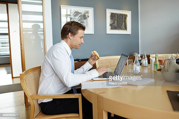"""Businessman doing """"working lunch"""" with laptop"""