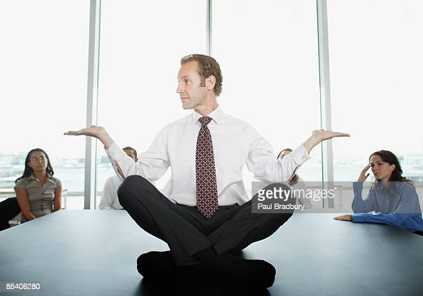 Businessman doing yoga in conference room