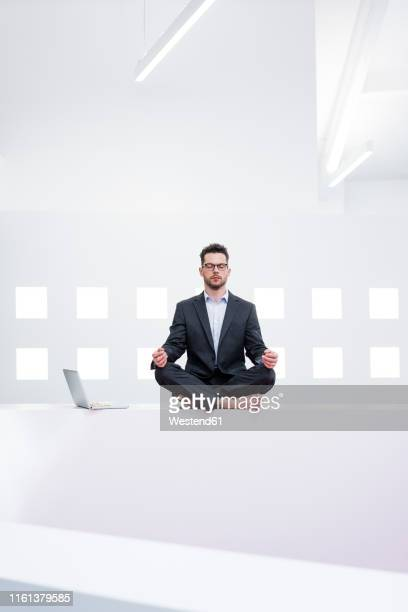 businessman doing yoga in office next to laptop - 胡坐 ストックフォトと画像