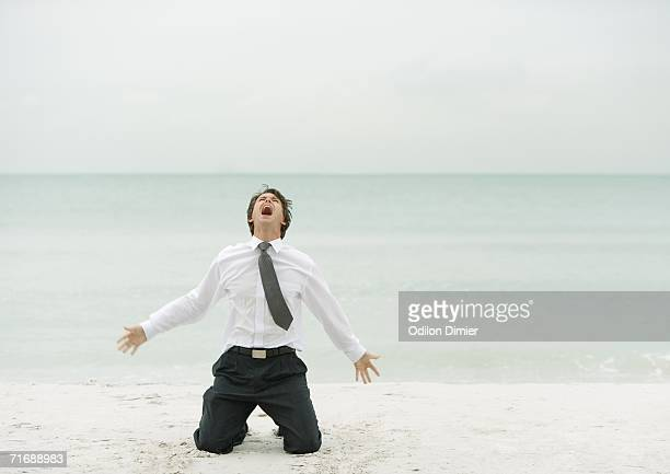 Businessman down on knees, screaming, on beach