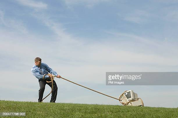 Businessman dragging old computer across field with rope