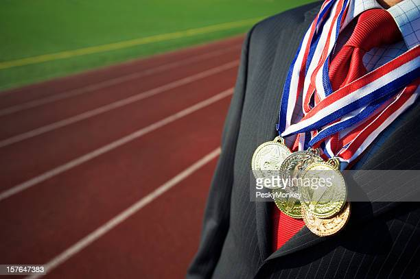 Businessman Draped with Medals Running Track Background