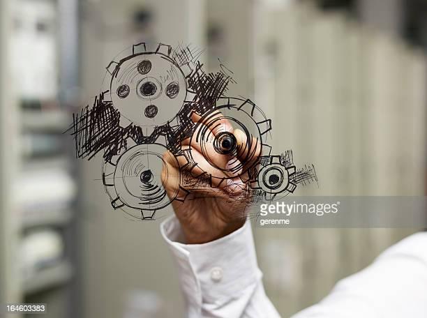 Businessman drawing gear wheel.