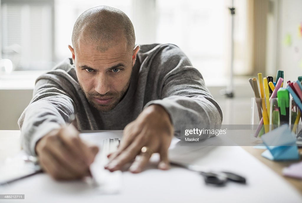 Businessman drawing line on paper at desk in creative office : Stock Photo