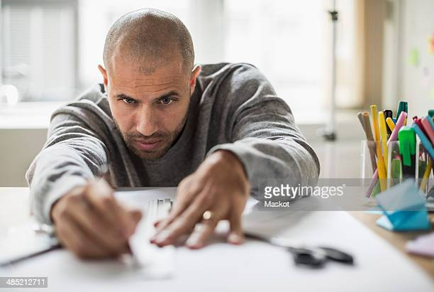 Businessman drawing line on paper at desk in creative office