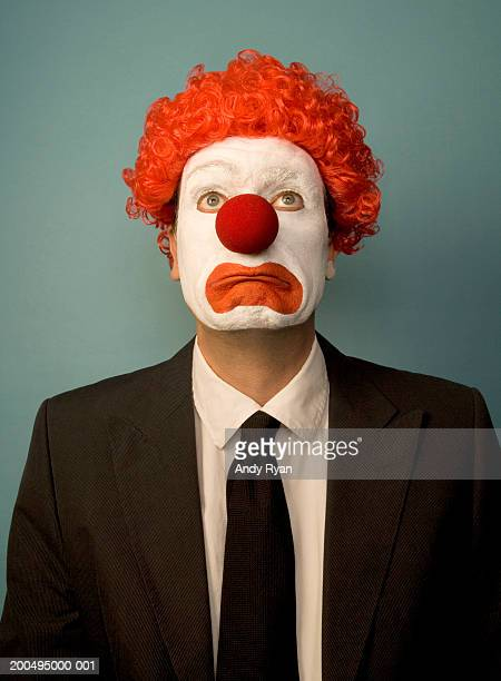 businessman dressed as clown, looking sad, front view, portrait - sad clown stock photos and pictures