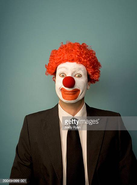Businessman dressed as clown, smiling, front view, portrait