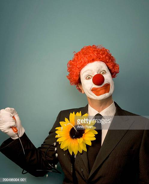 businessman dressed as clown squirting water from novelty flower - squirt foto e immagini stock