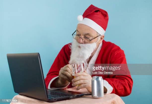 businessman dressed as santa claus at work using computer - aluhut stock-fotos und bilder