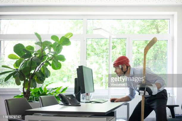 businessman dressed up as ice hockey player working at desk in office - ice hockey glove stock pictures, royalty-free photos & images