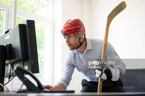 businessman dressed up as ice hockey player working at desk in office - ice hockey player stock pictures, royalty-free photos & images