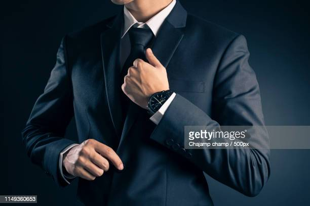 businessman dressing up a black suit - giacca nera foto e immagini stock