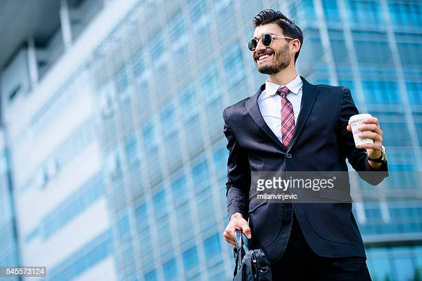 Businessman drinking a coffee to go outdoors