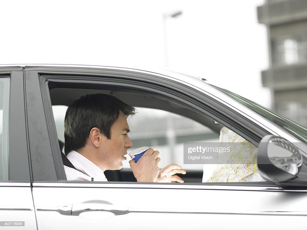 Businessman Drinking a Cup of Coffee Sitting in His Car and Looking at a Map : Stock Photo