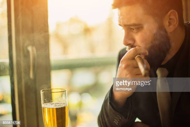 businessman drinking and smoking cigar at the bar - alcoholics anonymous stock pictures, royalty-free photos & images