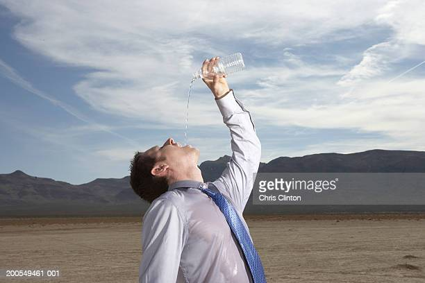 businessman drinking bottled water in dry lake bed - head back stock pictures, royalty-free photos & images