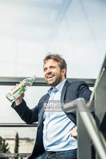 Businessman drinking bottled water on office stairway