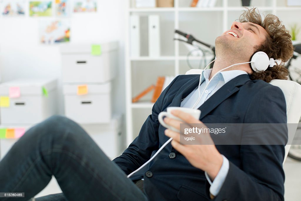 Businessman drinking coffee and listening music in office. : Stock Photo