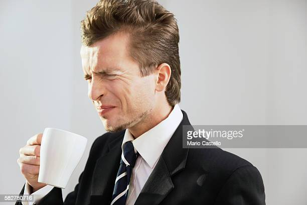Businessman drinking coffee and making face