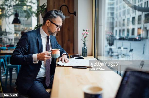 businessman drinking coffee and reading newspaper at cafe - 知能 ストックフォトと画像