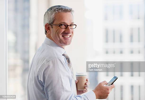 businessman drinking coffee and text messaging on cell phone - tourner photos et images de collection