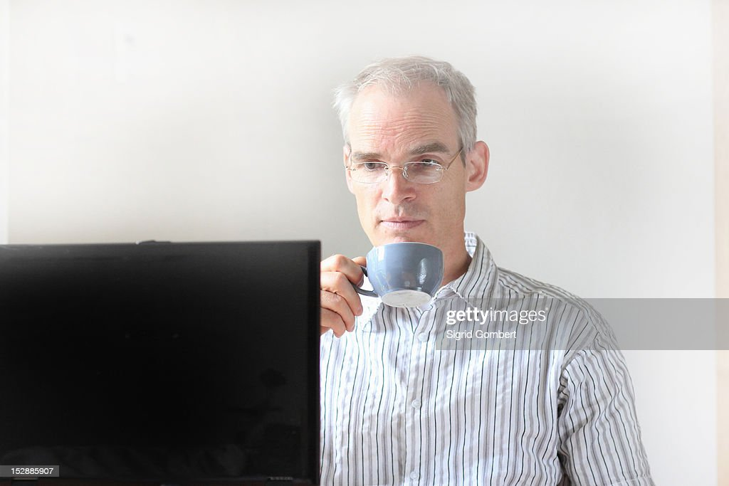 Businessman drinking coffee at computer : Stock-Foto