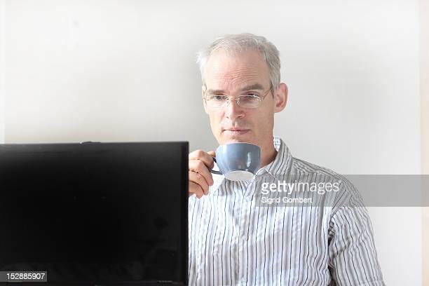 businessman drinking coffee at computer - sigrid gombert stock-fotos und bilder
