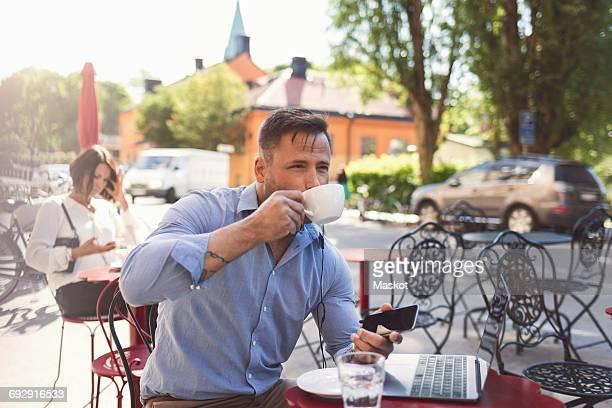 Businessman drinking coffee at sidewalk cafe