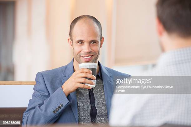 Businessman drinking coffee in airport