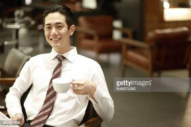 Businessman drinking coffee in hair salon