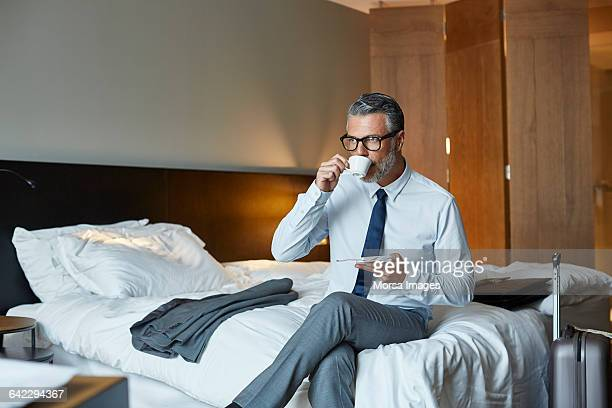 Businessman drinking coffee on bed in hotel room