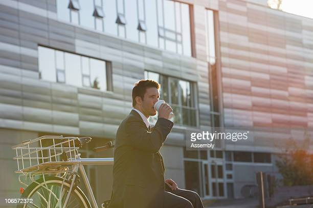 businessman drinking coffee outside office
