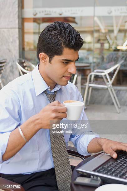 Businessman drinking coffee while using a laptop at a sidewalk cafe, Gurgaon, Haryana, India