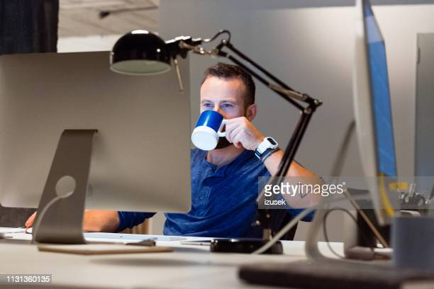 businessman drinking coffee while using computer - izusek stock pictures, royalty-free photos & images