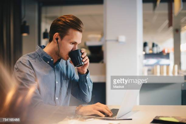 Businessman drinking coffee while using laptop at desk in office