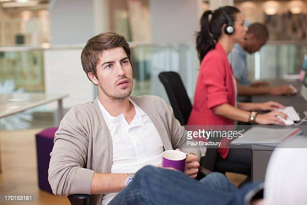 Uomo d'affari di bere il caffè in ufficio con piedi