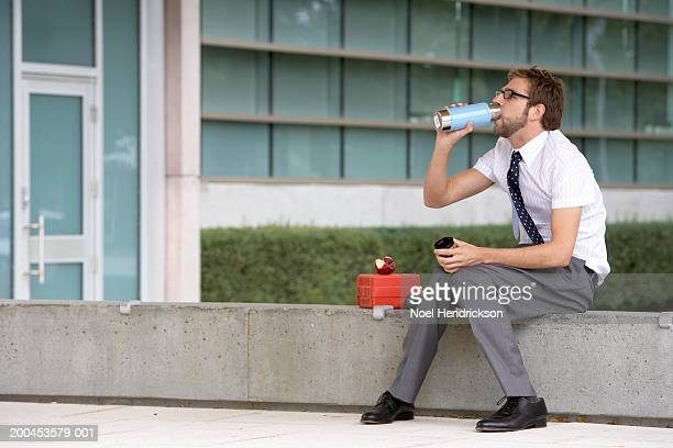 Businessman drinking from thermos