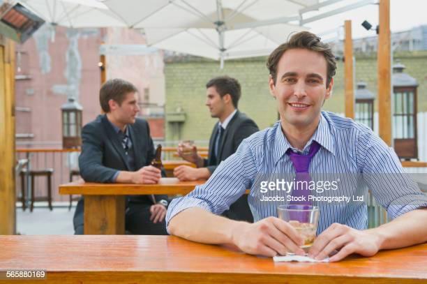 Businessman drinking in bar patio