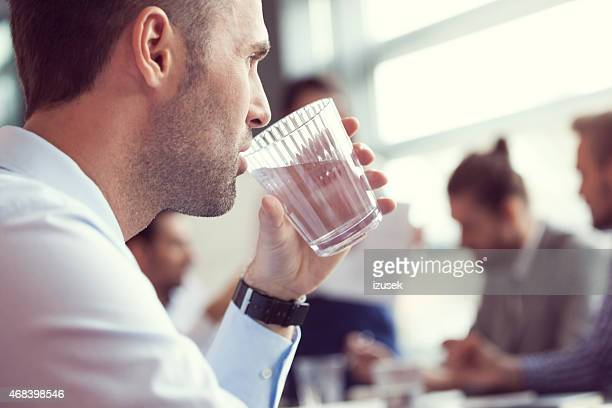 Businessman drinking water at the meeting