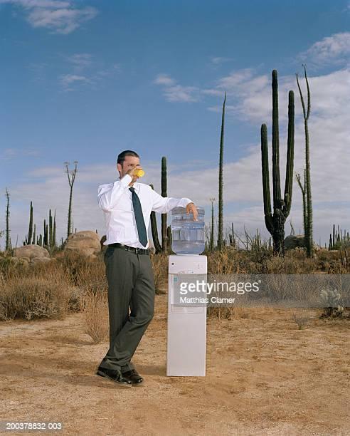 businessman drinking water near water cooler in desert - representar - fotografias e filmes do acervo