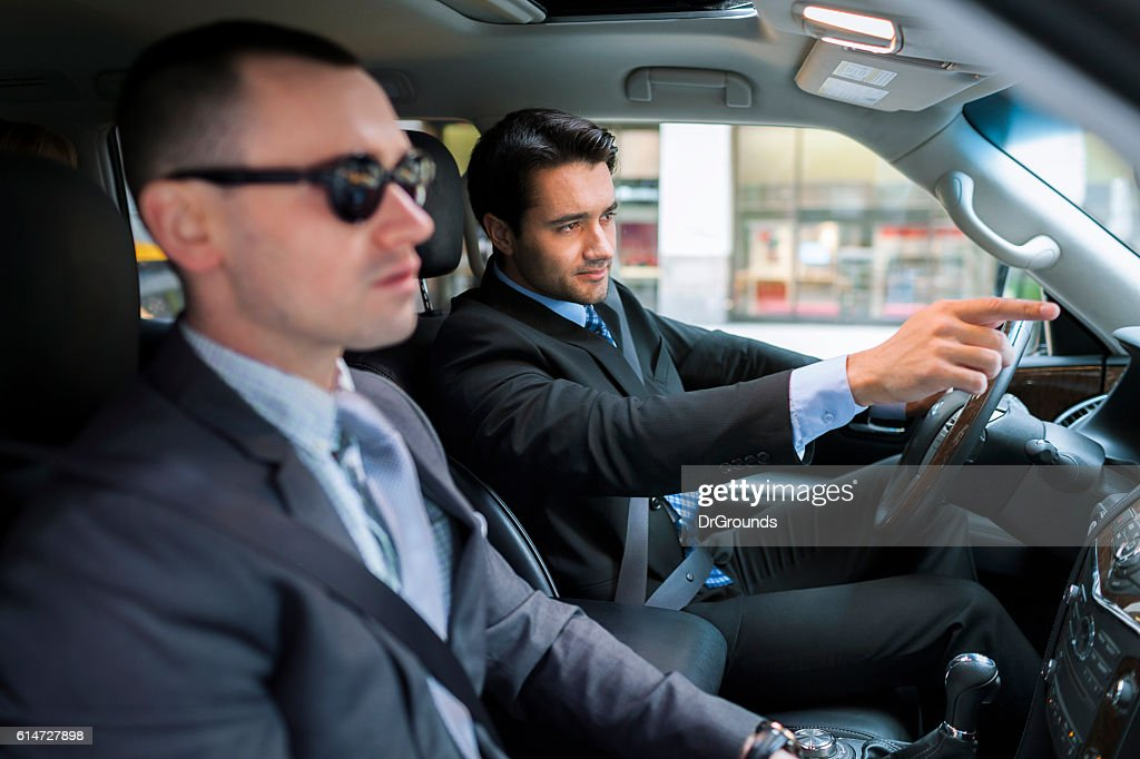 Businessman driver pointing something to his partner : Stock Photo