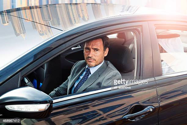 Businessman driving a car in Dubai Marina.