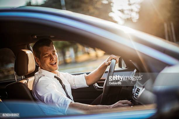 businessman driving a car - singing stock pictures, royalty-free photos & images