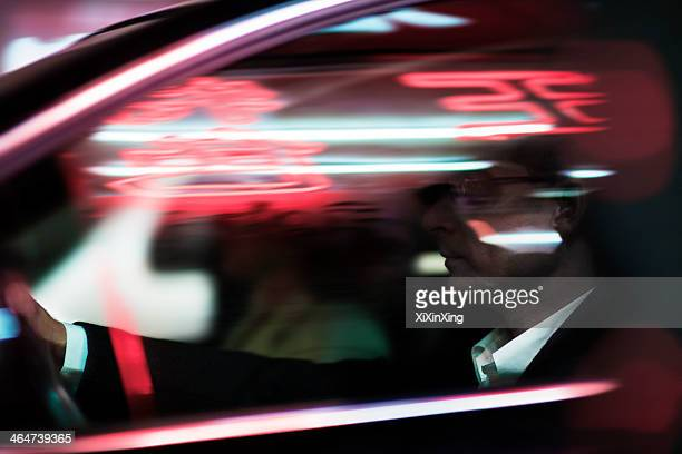 Businessman driving at night, illuminated and reflected lights on the car window