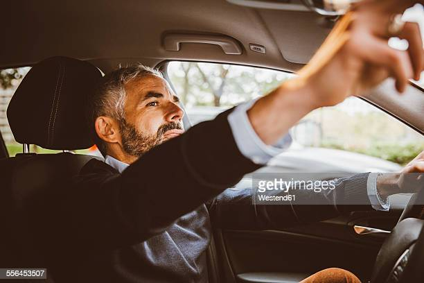 Businessman driving car adjusting rear view mirror