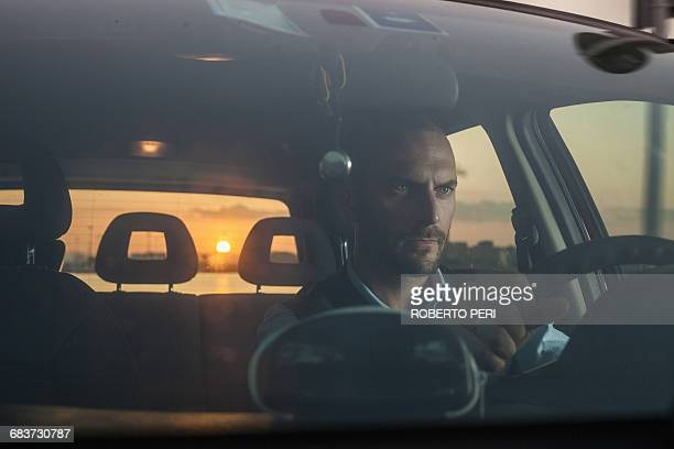 Businessman driving car on coast at sunset, Cagliari, Sardinia, Italy