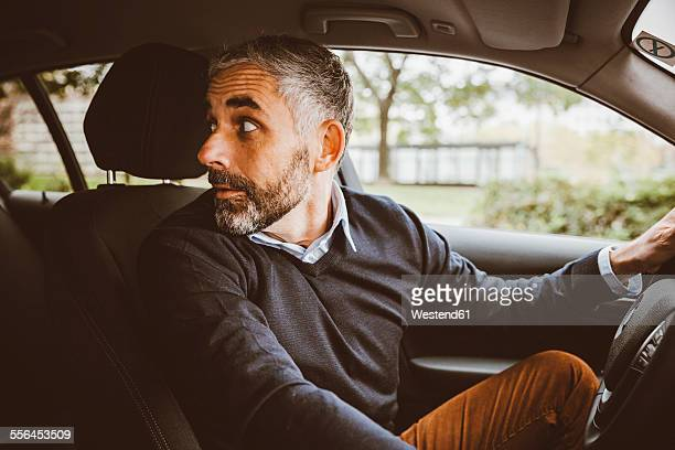 Businessman driving car turning round