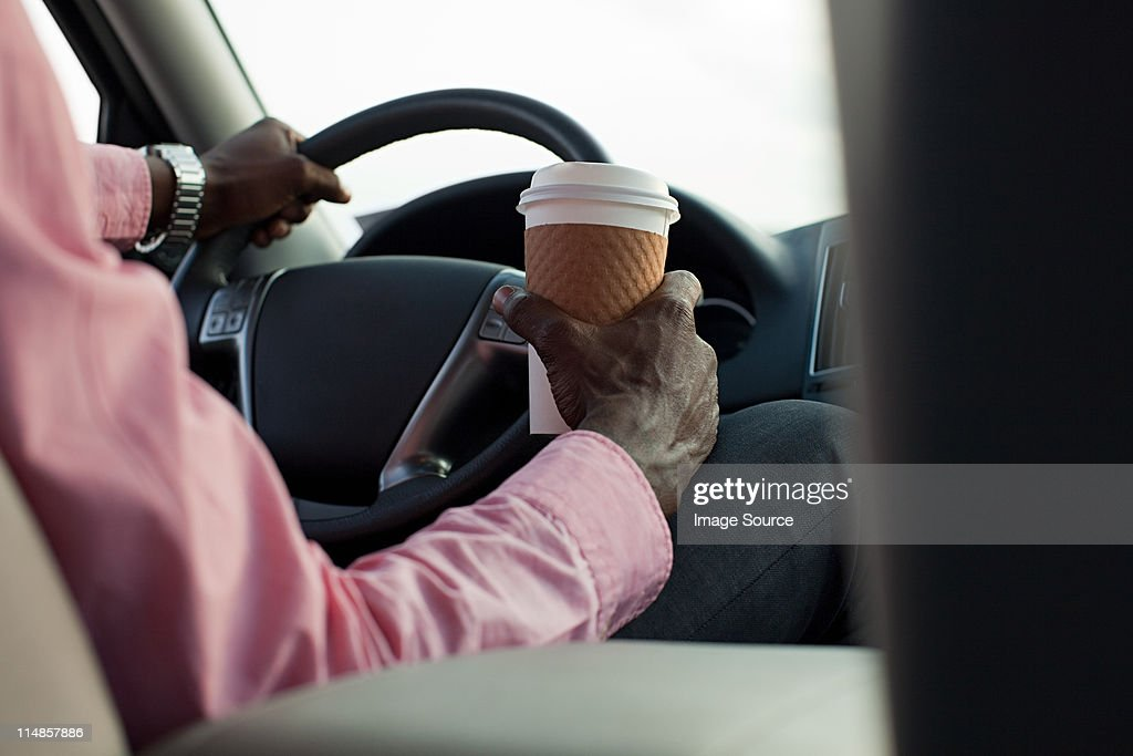 Businessman driving car with disposable cup : Stock Photo