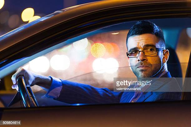 Businessman driving his car by night