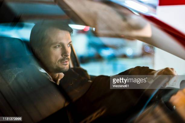 businessman driving in his car at night - one man only stock pictures, royalty-free photos & images